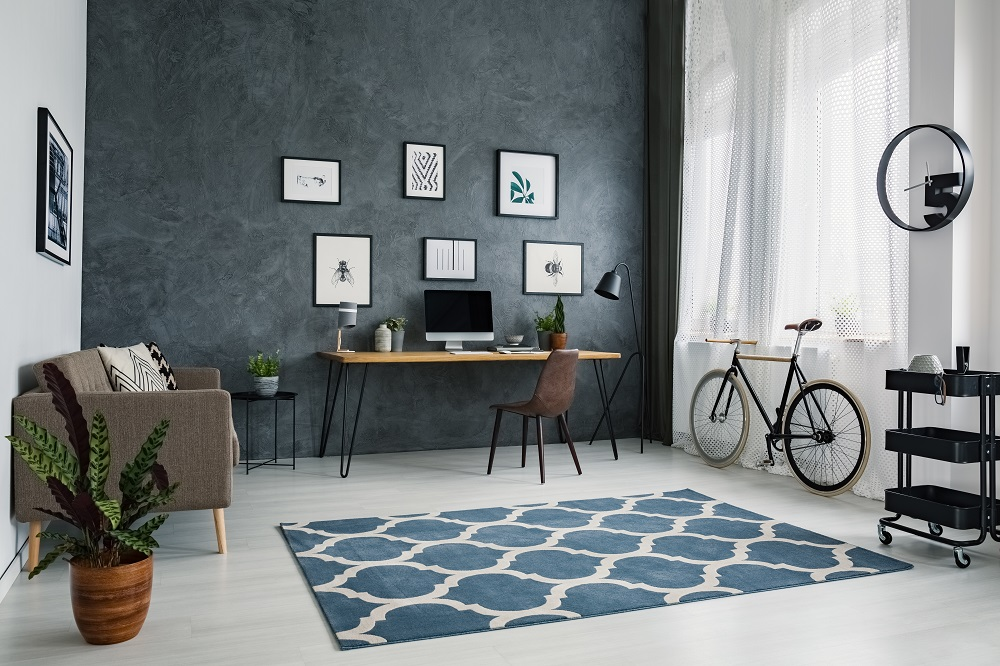 Patterned carpet in bright workspace interior with bicycle next to brown chair at desk.